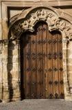 与铁匠的钉子的古老门在与有裂片的曲拱的一个门面 图库摄影