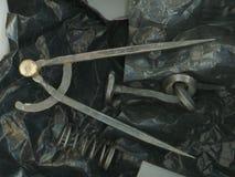与铁尖顶和轮尺的难看的东西黑静物画 免版税库存照片