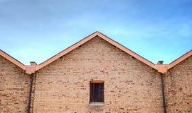 与铁棍的老砖瓦房在窗口里 库存照片