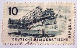 与铁货车和采矿活动的图象的老蓝色东德邮票 免版税图库摄影