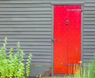 与铁通道门环的明亮的红色木门和在殖民地大厦墙壁的钉子装饰  免版税库存照片