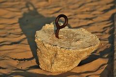 与铁锈在海滩埋置的里面色的螺丝圈的混凝土板 库存图片