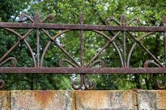 与铁锈的伪造的金属格栅在篱芭 免版税库存照片