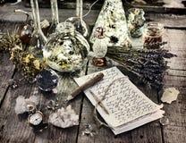 与铅笔、不可思议的瓶、水晶、老时钟和淡紫色的巫婆原稿在板条开花 免版税图库摄影
