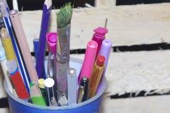 与铅笔、毡尖的笔和把柄的一块玻璃在地板上站立由木板制成 免版税库存图片