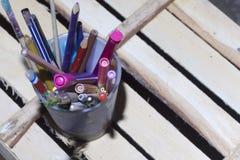 与铅笔、毡尖的笔和把柄的一块玻璃在地板上站立由木板制成 库存图片