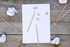 与铅笔削片的白纸在木桌上 免版税库存照片