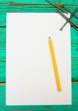 与铅笔和工具的纸在木 免版税库存图片