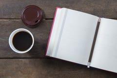 与铅笔和无奶咖啡的红色被盖的被打开的书空白页 库存图片