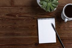 与铅笔的一个空白的笔记薄,用咖啡和植物木背景的 库存照片