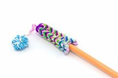与铅笔的五颜六色的有弹性彩虹织布机带 库存图片