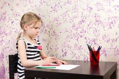 与铅笔的小女孩图画在桌上 库存照片