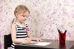 与铅笔的小女孩图画在桌上 免版税库存图片