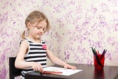 与铅笔的小女孩图画在桌上 免版税库存照片
