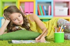 与铅笔的小女孩绘画在她的屋子里 库存图片
