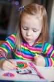 与铅笔的小的逗人喜爱的女孩绘画,当时 免版税图库摄影