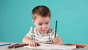 与铅笔的愉快的儿童图画在册页,隔绝在蓝色 股票视频