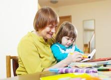 与铅笔的愉快的祖母和儿童图画 库存照片