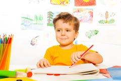 与铅笔的男孩图画在本文在桌上 免版税库存照片