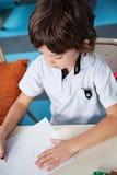 与铅笔的男孩图画在艺术课的纸 免版税图库摄影