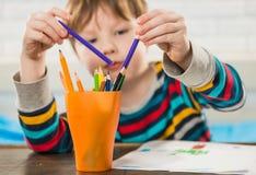 与铅笔的男孩图画 免版税库存图片