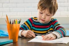 与铅笔的男孩图画 免版税库存照片