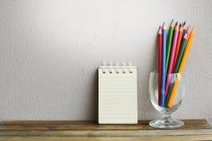 与铅笔的笔记薄在木委员会背景 使用教育的墙纸,企业照片 注意到书的产品与 图库摄影