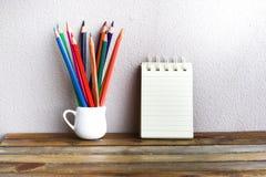 与铅笔的笔记薄在木委员会背景 使用教育的墙纸,企业照片 注意到书的产品与 免版税图库摄影