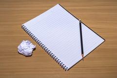 与铅笔的笔记薄在木桌上 免版税库存图片