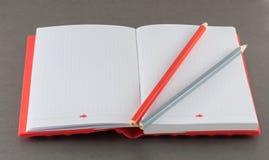与铅笔的笔记薄在灰色背景 免版税库存照片