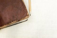 与铅笔的老皮革葡萄酒书在简单的粗麻布背景 免版税库存照片