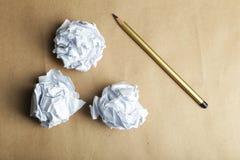 与铅笔的被弄皱的纸球在棕色背景 免版税库存图片