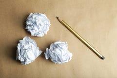 与铅笔的被弄皱的纸球在棕色背景 免版税库存照片