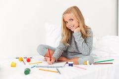 与铅笔的迷人的小女孩图画在白色床上,看 库存照片