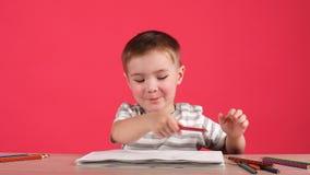 与铅笔的逗人喜爱的男婴图画在桃红色背景的册页 股票录像