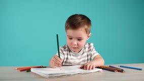 与铅笔的逗人喜爱的男婴图画在蓝色背景的册页 影视素材