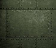 与铆钉的军事绿色金属装甲背景 库存照片