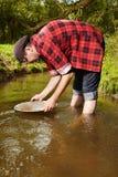 与铝平底锅金子的探油矿者摇摄在小河 库存图片