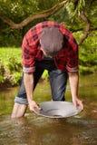与铝平底锅金子的探油矿者摇摄在小河 库存照片