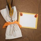 与银器、餐巾、麦子和一张黄色和白色名片的愉快的万圣夜表餐位餐具与逗人喜爱的南瓜装饰 库存图片