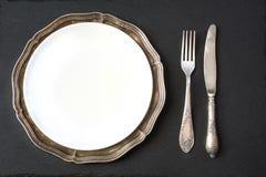 与银器的葡萄酒盘在板岩背景 餐位餐具表 免版税图库摄影