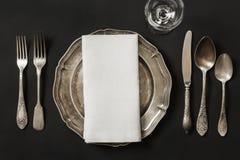 与银器的葡萄酒盘在黑背景的午餐的 餐位餐具表 免版税库存照片