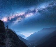 与银河、女孩和山的空间在晚上 免版税库存照片