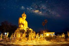 与银河、菩萨雕象和烛光队伍的夜 库存照片