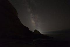 与银河的海洋岩石 免版税图库摄影
