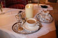 与银的咖啡在与蜡烛的表上 免版税库存图片