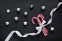 与银色丝带的圣诞节在黑背景的糖果和球 抽象空白背景圣诞节黑暗的装饰设计模式红色的星形 顶视图和拷贝空间 免版税库存照片