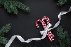 与银色丝带的圣诞节糖果和在黑背景的绿色杉树 抽象空白背景圣诞节黑暗的装饰设计模式红色的星形 顶视图 库存图片