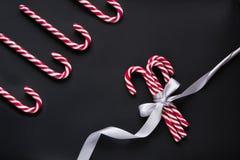 与银色丝带的圣诞节糖果在黑背景 抽象空白背景圣诞节黑暗的装饰设计模式红色的星形 顶视图和拷贝空间 免版税库存照片