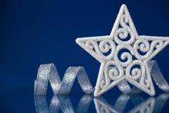 与银色丝带的白色圣诞节星在与空间的蓝色背景文本的 免版税库存照片